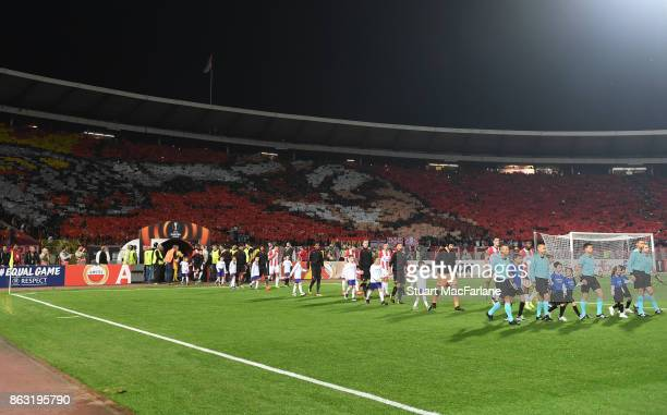 The Arsenal and Red Star teams walk out before the UEFA Europa League group H match between Crvena Zvezda and Arsenal FC at Rajko Mitic Stadium on...
