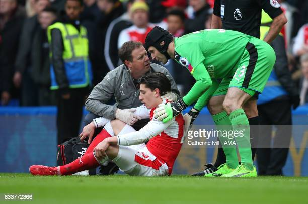 The Arsenal medic confers with Petr Cech of Arsenal as Hector Bellerin of Arsenal is treated for an injury during the Premier League match between...