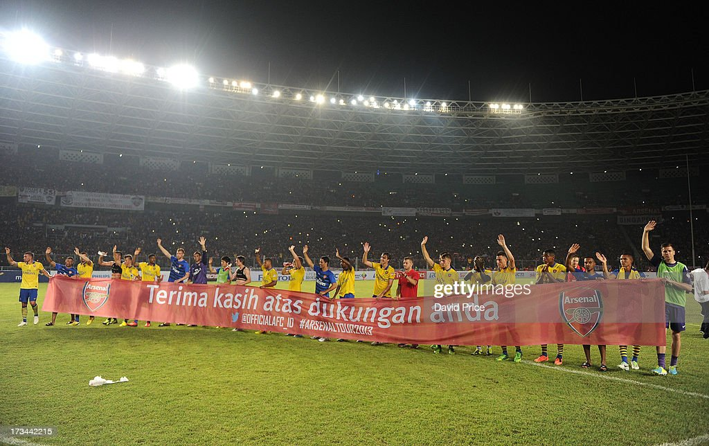 The Arsenal players hold up a banner to thank the fans after the match between Arsenal and the Indonesia All-Stars at Gelora Bung Karno Stadium on July 14, 2013 in Jakarta, Indonesia.