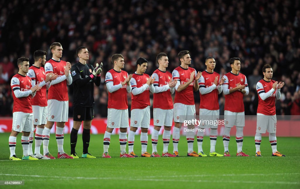 The Arsenal players take part in a minutes applause in honour of Nelson Mandela before the Arsenal against Everton Premier League match at Emirates Stadium on December 8, 2013 in London, England.