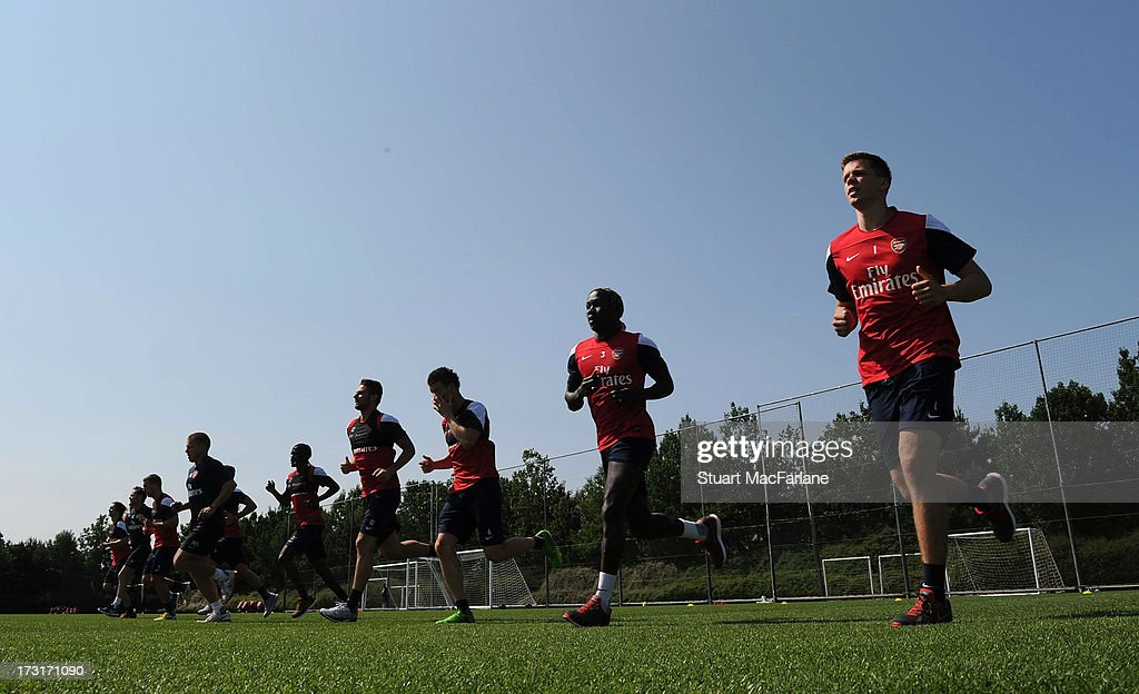 The Arsenal players warm up before a training session at London Colney on July 09, 2013 in St Albans, England.