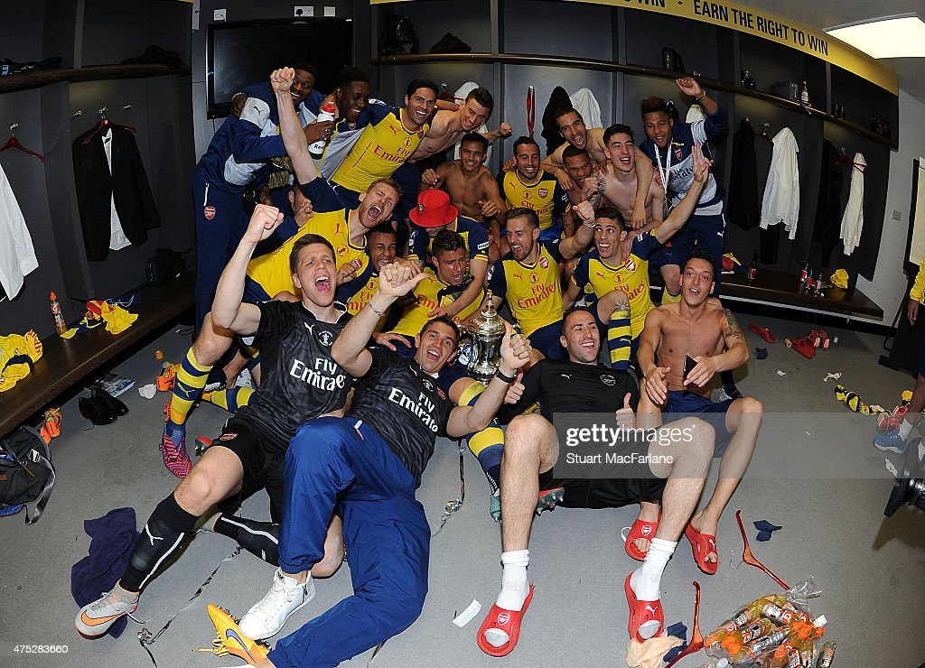 The Arsenal squad celebrate in the dressing room after winning the Cup after the FA Cup Final between Aston Villa and Arsenal at Wembley Stadium on May 30, 2015 in London, England.