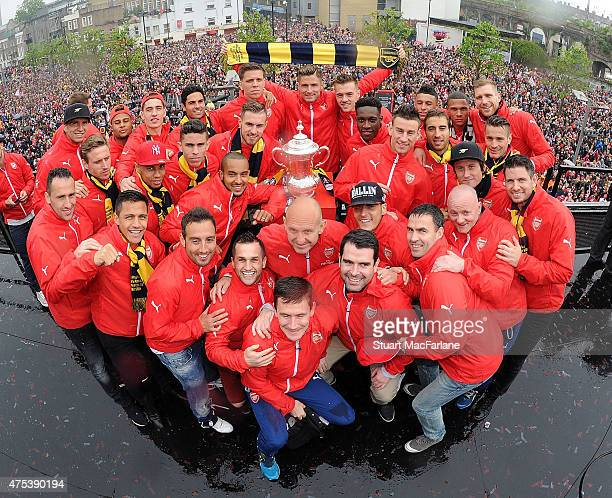 The Arsenal squad pose with the cup during the Arsenal FA Cup Victory Parade in Islington on May 31 2015 in London England
