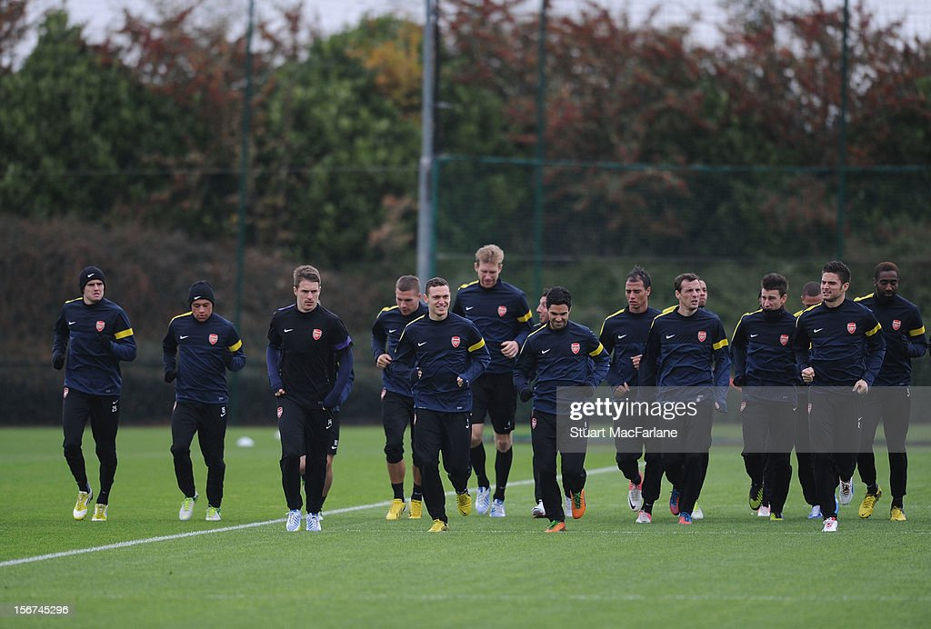 The Arsenal squad warm up before a training session at London Colney on November 20, 2012 in St Albans, England.
