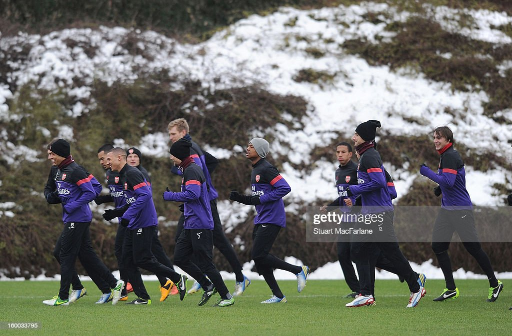 The Arsenal squad warm up before a training session at London Colney on January 25, 2013 in St Albans, England.