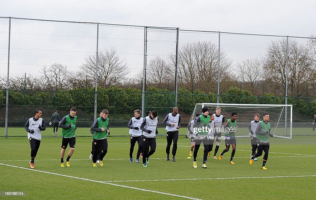 The Arsenal squad warm up before a training session at London Colney on March 15, 2013 in St Albans, England.
