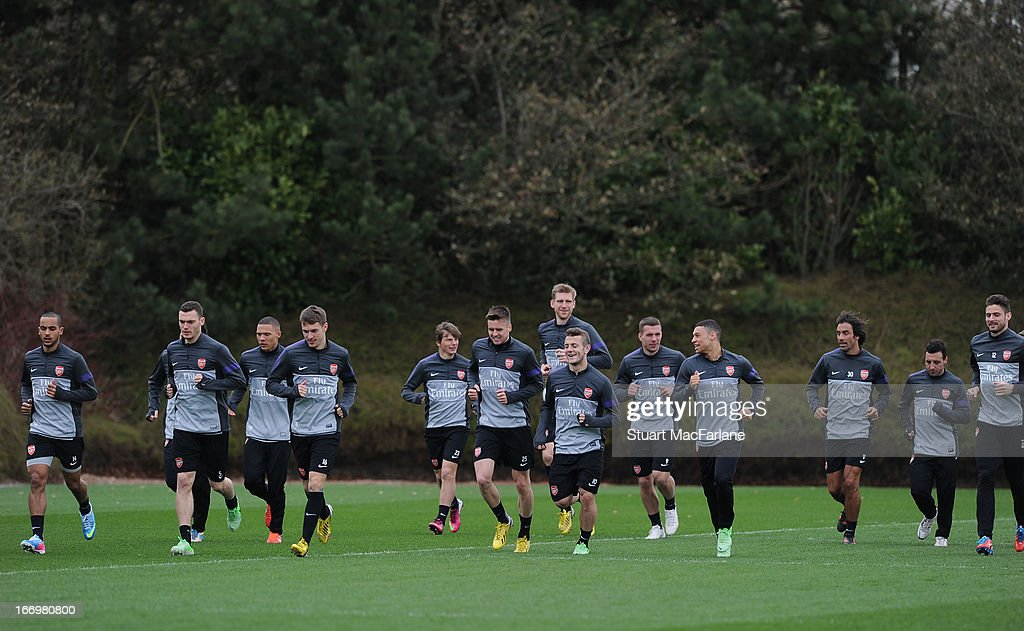 The Arsenal squad warm up before a training session at London Colney on April 19, 2013 in St Albans, England.
