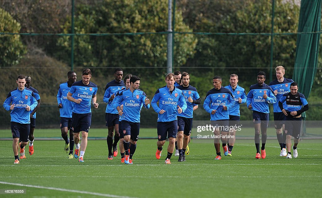 The Arsenal squad warm up before a training session at London Colney on April 5, 2014 in St Albans, England.