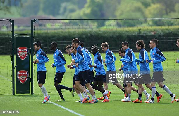 The Arsenal squad warm up before a training session at London Colney on April 27 2014 in St Albans England