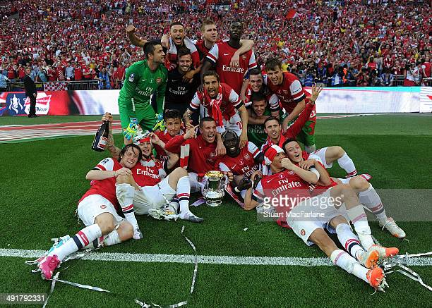 The Arsenal team lift the FA Cup after the match between Arsenal and Hull City at Wembley Stadium on May 17 2014 in London England