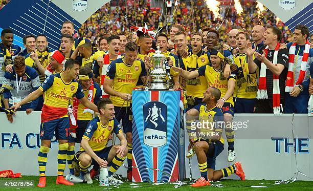 The Arsenal team pose with the trophy after winning the FA Cup final football match between Aston Villa and Arsenal at Wembley stadium in London on...