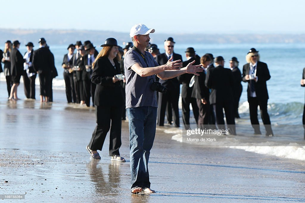 The artist (C) directs participants as they stand on the beach in suits and bowler hats as part of an art installation created by surrealist artist Andrew Baines on January 20, 2013 in Adelaide, Australia.