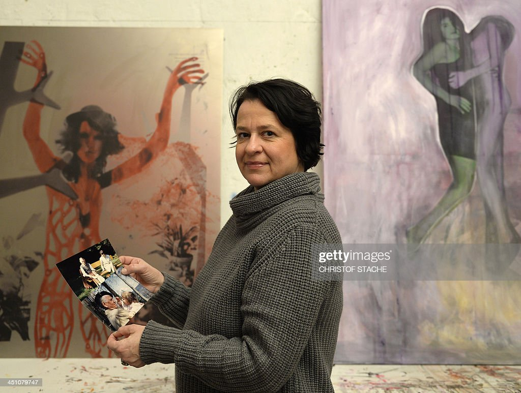 The artist Nana Dix, grand daughter of the German painter Otto Dix, poses with private photographs in front of her own works in her studio in Munich, southern Germany, on November 21, 2013. In an interview with AFP Nana Dix asks German authorities to publish the 1,406 works being seized in February 2012 at the Munich's flat of Cornelius Gurlitt, son of German art collector Hildebrand Gurlitt, an art dealer tasked by the Nazis with selling confiscated, looted and extorted art works in exchange for hard currency. Previously unknown masterpieces by modernist painter Otto Dix are among a vast trove of works believed stolen by the Nazis and uncovered in Gurlitt's flat.