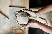 The artist sculpts a ball of clay