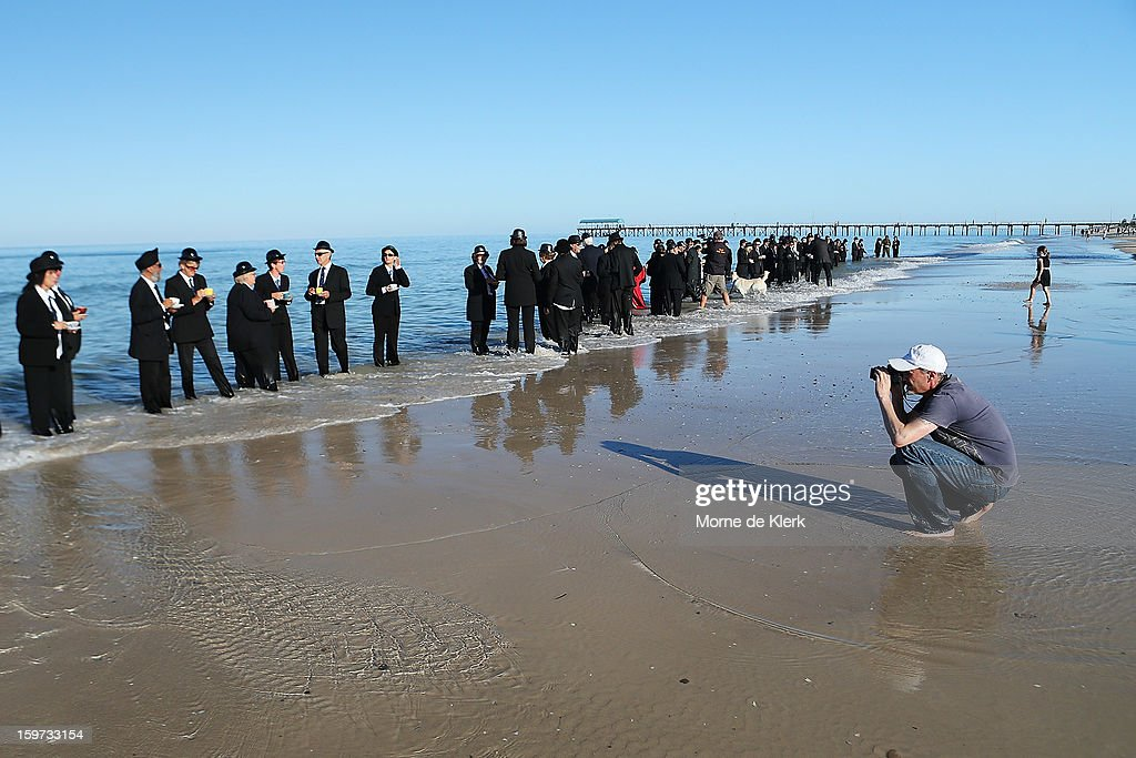 The artist (R) takes reference pictures as participants stand on the beach in suits and bowler hats as part of an art installation created by surrealist artist Andrew Baines on January 20, 2013 in Adelaide, Australia.