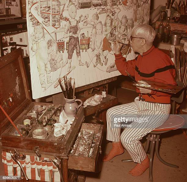 The artist Tsougharu Foujita at work on a painting of children playing France 1958
