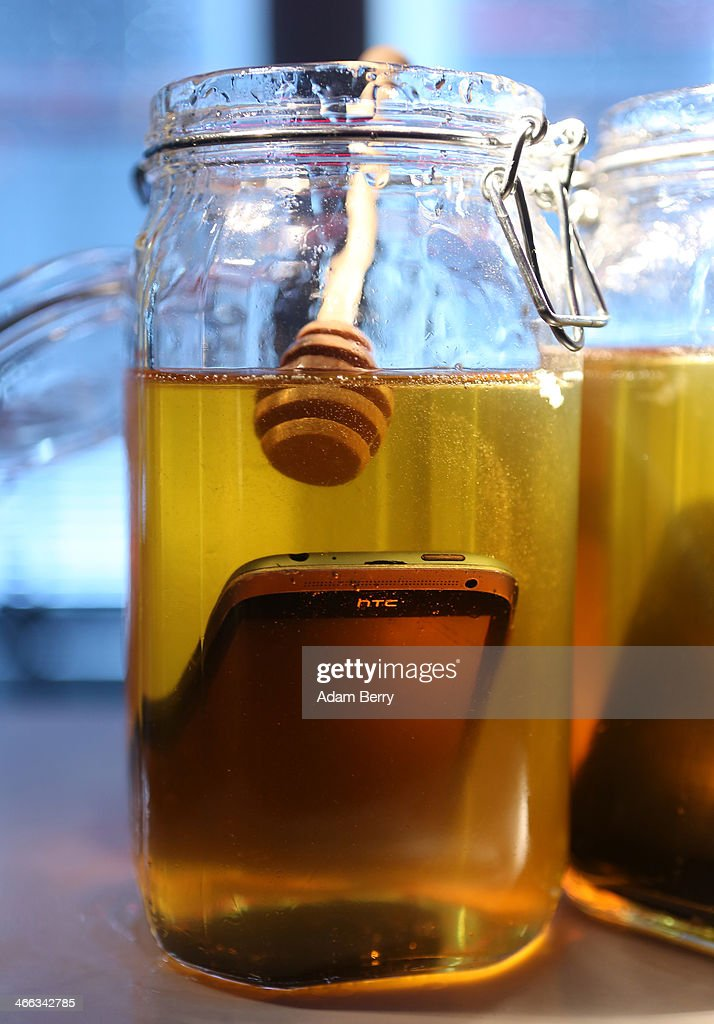 The artwork 'Honeypot' by Robert Boehnke and Johan Uhle, featuring two smartphones submerged in honey jars, sits on display at the Transmediale festival for art and digital culture on February 1, 2014 in Berlin, Germany. The festival and year-round project is an attempt to draw out new connections between art, culture and technology.