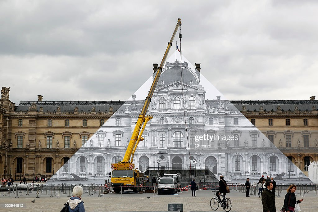 The artwork of French street artist JR is displayed on the Louvre Pyramid on May 24, 2016 in Paris France. French street artist JR has installed a huge photographic collage on the Louvre pyramid, for making it disappear and creating a giant optical illusion through an anamorphosis, a technique that allows to appear or disappear a work.