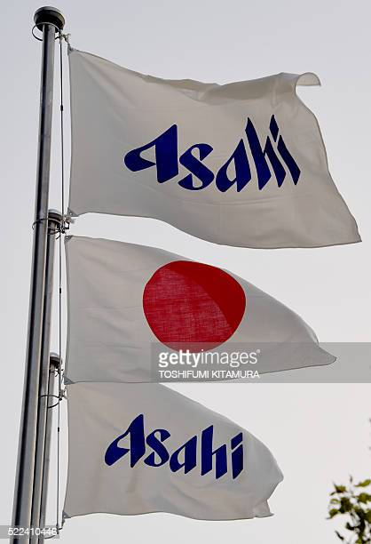 The Asahi flags fly with the Japanese national flag beside the Asahi Breweries headquarters building in Tokyo on April 19 2016 Japanese beer giant...