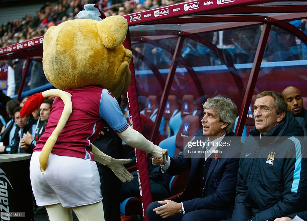 The Aston Villa mascot, Bella the Lion greets Manuel Pellegrini the manager of Manchester City prior to the Barclays Premier League match between Aston Villa and Manchester City at Villa Park on November 8, 2015 in Birmingham, England.