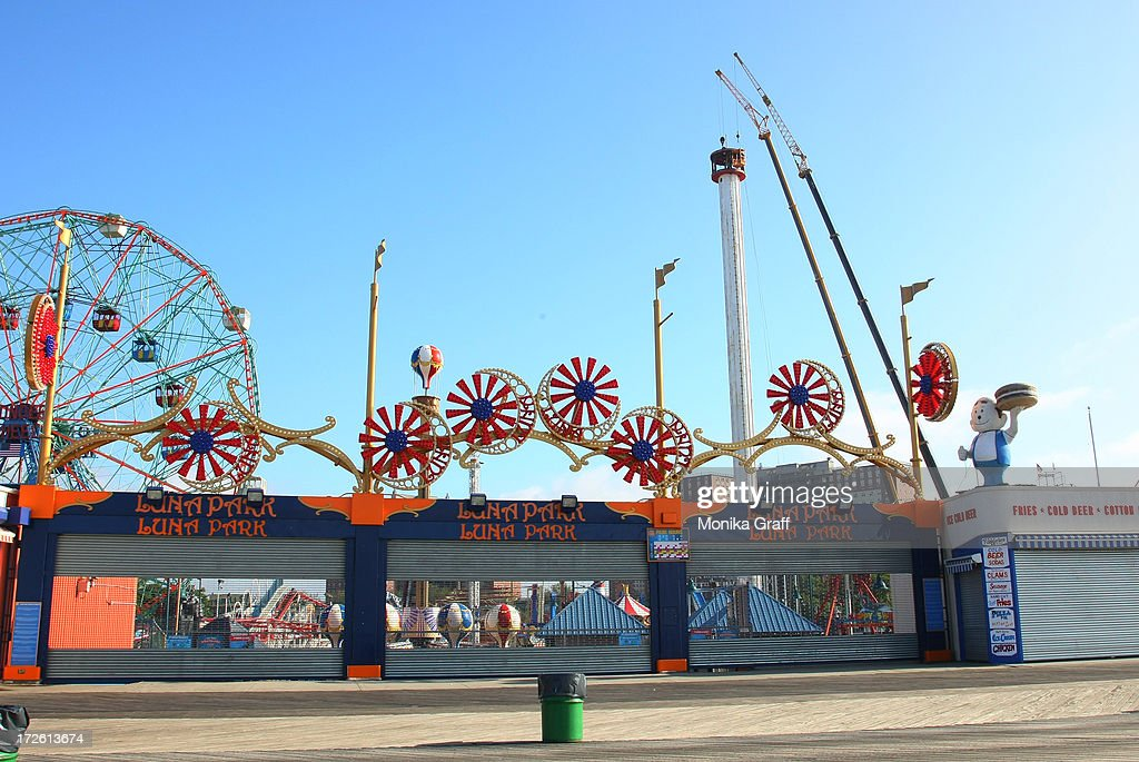 The Astrotower (right) is worked on as Luna Park remains closed in Coney Island on July 4, 2013 in the Brooklyn borough of New York City. Officials decided to close Luna Park and sections of the boardwalk while workers take down the amusement tower which was seen precariously swaying two days ago.