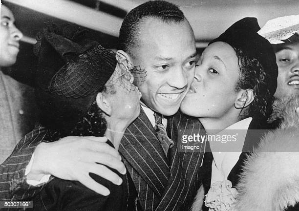 The athlete Jesse Owens is greeted upon his return by the Olympic Games by his mother and his wife New York 1st September 1936 Photograph