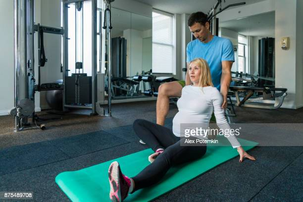 The athletic man, personal trainer, do fitness stretching relaxing shoulders massage for a pretty pregnant woman in the gym.