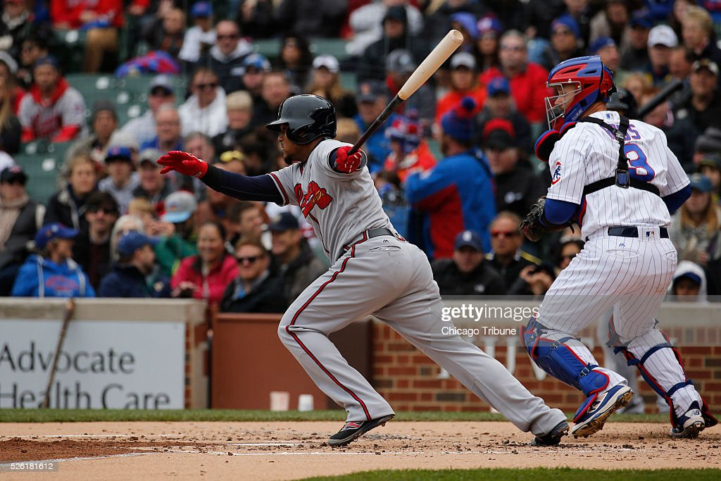 The Atlanta Braves' Erick Aybar singles in the second inning as Chicago Cubs catcher David Ross (3) looks on at Wrigley Field in Chicago on Friday, April 29, 2016. The Cubs won, 6-1.