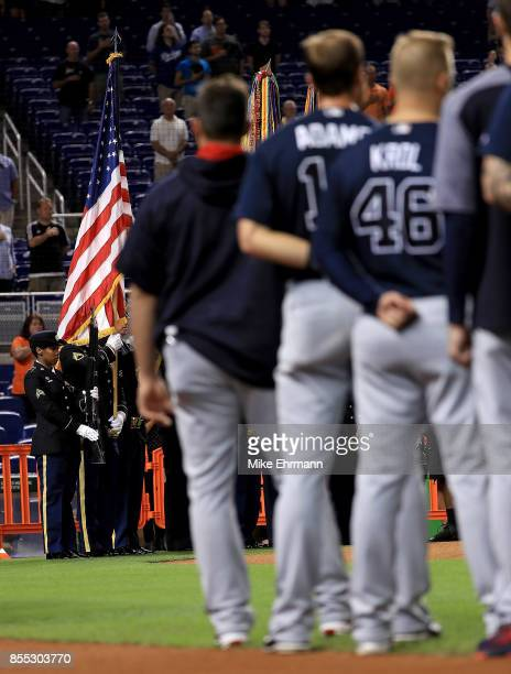 The Atlanta Braves stand during the National Anthem during a game against the Miami Marlins at Marlins Park on September 28 2017 in Miami Florida