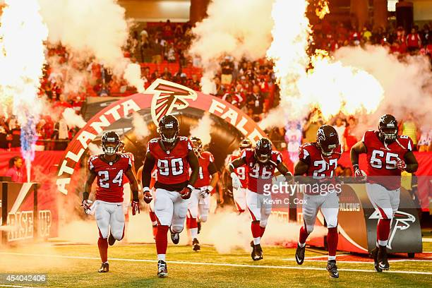 The Atlanta Falcons run out on the field prior to a preseason game against the Tennessee Titans at the Georgia Dome on August 23 2014 in Atlanta...