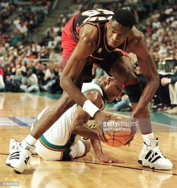 The Atlanta Hawks' Dikembe Mutombo pulls a loose ball away from the Detroit Pistons' Terry Mills in the first quarter 02 May at the Palace in Auburn...