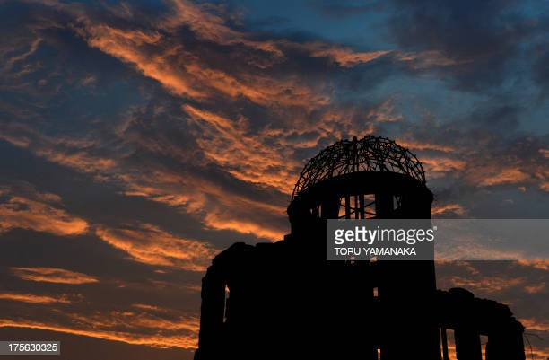 The Atomic Bomb Dome is seen in silhouette during sunset over the Peace Memoral Park in Hiroshima on August 5 2013 Tens of thousands of people were...