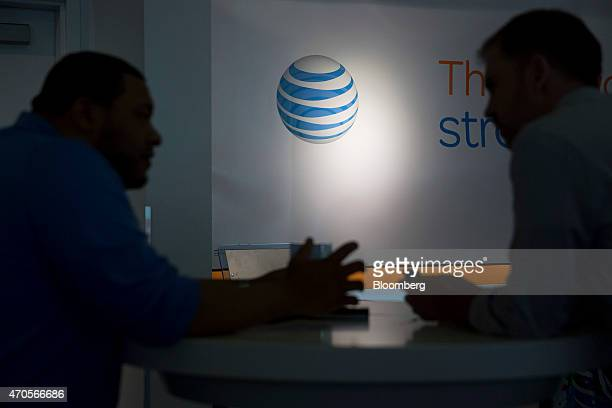The ATT Inc logo is seen past a customer and a retail sales consultant at an ATT store in Washington DC US on Tuesday April 21 2015 ATT Inc the...