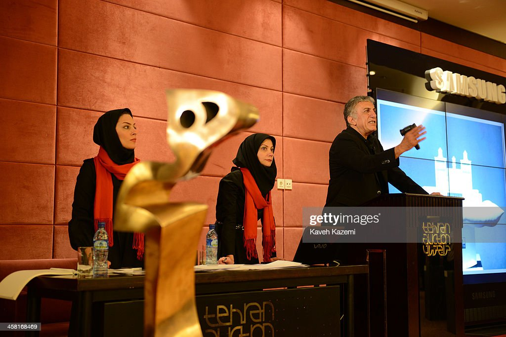 The auctioneer and veiled aids seen during a contemporary art auction by famous Iranian artists in the dinning hall of Azadi Hotel on June 28, 2013 in Tehran, Iran.