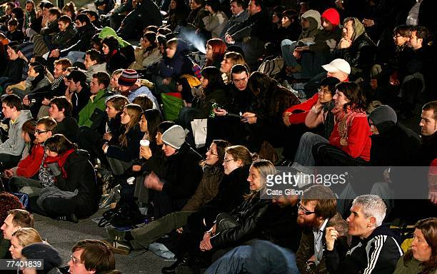 The audience in Trafalgar Square watches as pianist Neil Brand provides the accompaniment to archive films being shown on the big screen on October...