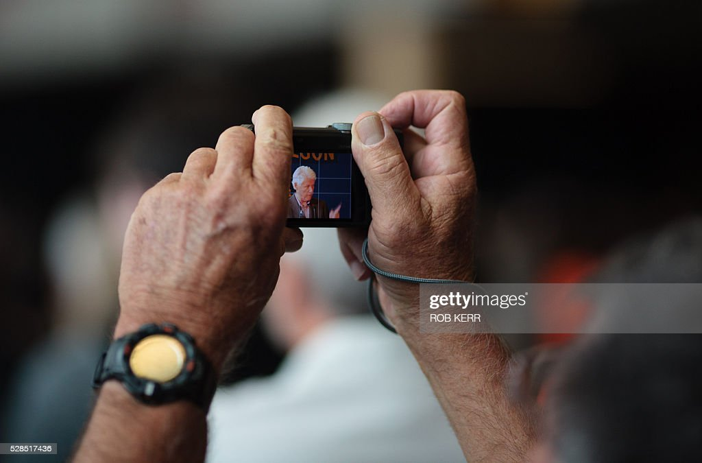 The audience listend and photographs former US President Bill Clinton as he speaks at Central Oregon Community College while campaigning for US Democratic presidential candidate Hillary Clinton on May 5, 2016, in Bend, Oregon. / AFP / Rob Kerr