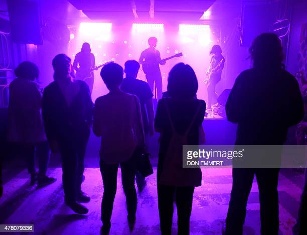 The audience listens as members of the Chinese Punk Rock band 'Birdstriking' Wen Yuzhen guitarist He Fan lead vocalist guitar and Zhou Nairen bass...