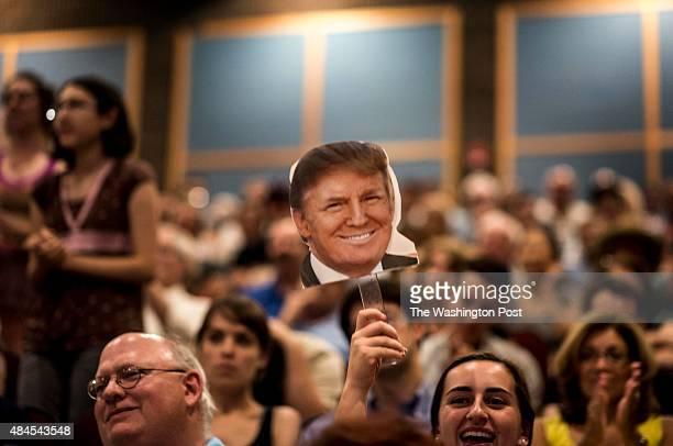 The audience stands and waves in support of Donald Trump in a crowded auditorium at a town hall meeting in Derry New Hampshire on Wednesday August 19...