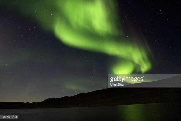 The Aurora Borealis glows over a lake September 02 near the Greenland town of Kangerlussuaq The Northern Lights most often occurs from September to...