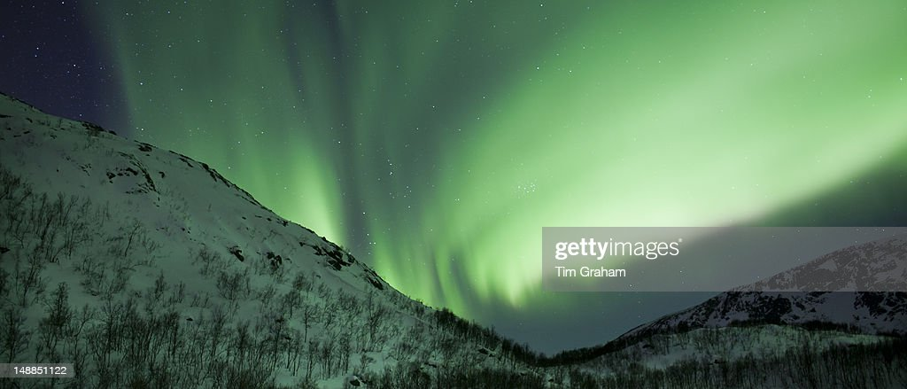 The Aurora Borealis the spectacular Northern Lights fill the sky with dazzling green light above Kvaloya island at Tromso in the Arctic Circle in...