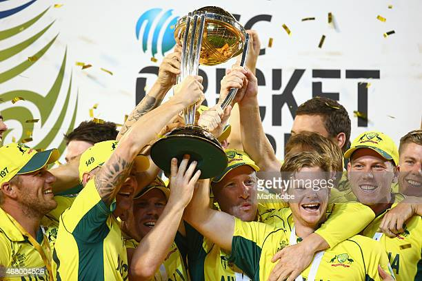 The Australia team cheer as they lift the world cup trophy as they celebrate victory during the 2015 ICC Cricket World Cup final match between...