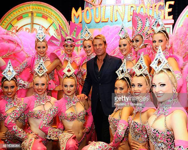 The Australian cricket champion Shane Warne poses backstage with the Moulin Rouge Australian dancers at Le Moulin Rouge on June 27 2014 in Paris...
