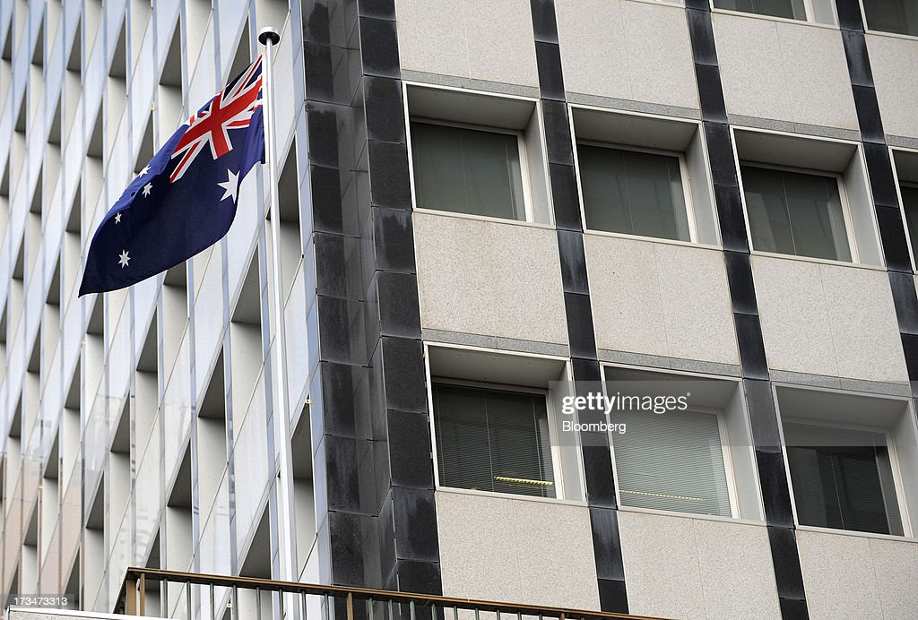 The Australian flag flies outside the Reserve Bank of Australia (RBA) headquarters in the central business district of Sydney, Australia, on Monday, July 15, 2013. While the RBA previously needed higher interest rates to control price pressures as the Australian economy expanded since 1991 without a recession, Governor Glenn Stevens has slashed the cash target, predicting a mining boom will wane. Photographer: Dan Himbrechts/Bloomberg via Getty Images