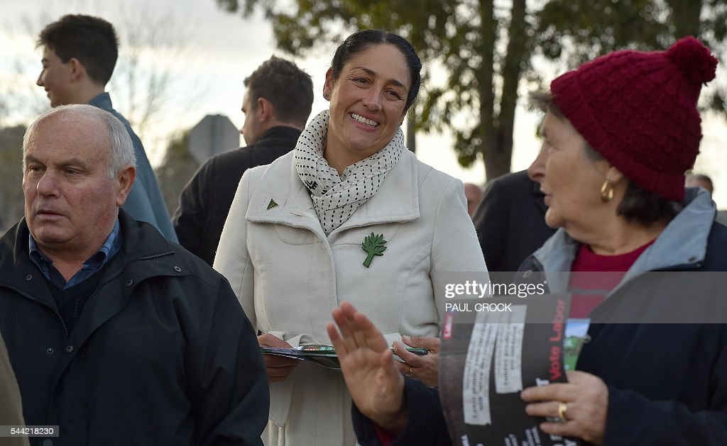 The Australian Greens Party candidate for the 'safe' Labor seat of Batman Alex Bhathal (C) tries to win over voters at a polling booth in the Australian Federal Election in Melbourne on July 2, 2016. Australia is voting in a general election which is expected to be a close race between the ruling Liberal-National coalition and the opposition Labor Party. / AFP / Paul Crock