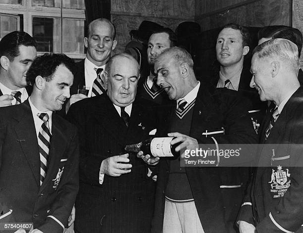 The Australian Kangaroos Rugby League team celebrating with Manager Norman Robinson pouring AgentGeneral J M Tulley a glass of champagne as captain...
