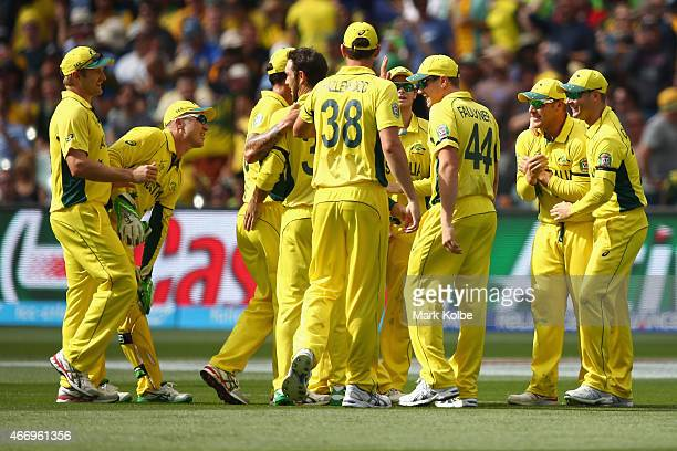 The Australian team congratulate Glenn Maxwell and Aaron Finch of Australia after they combined to take the wicket of Umar Akmal of Pakistan during...