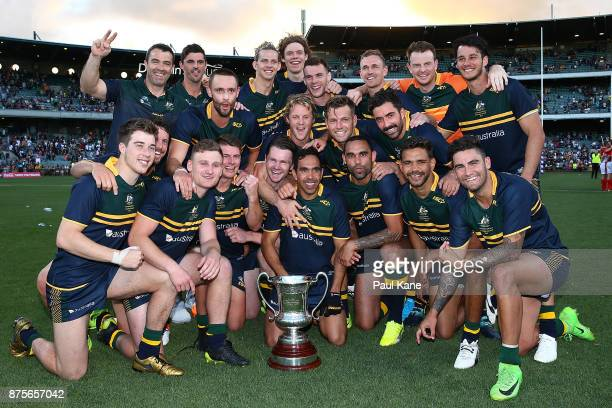 The Australian team pose with the Cormac McAnallen trophy after winning game two and the series of the International Rules Series between Australia...