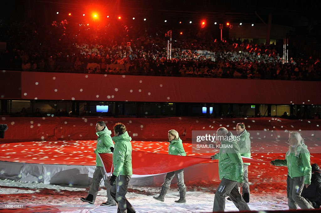 The Austrian delegation carries their country's flag during the opening ceremony of the FIS World Ski Championships on February 4, 2013 in Schladming. AFP PHOTO / SAMUEL KUBANI