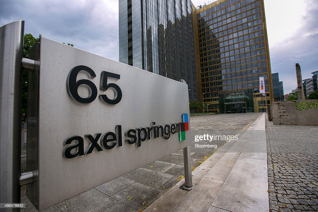 The Axel Springer SE logo sits on a sign outside the newspaper publisher's offices in Berlin, Germany, on Wednesday, June 11, 2014. Axel Springer, Europe's biggest newspaper publisher, is working with JPMorgan Chase & Co. and Citigroup Inc. on an initial public offering of its digital-classifieds business, people familiar with the matter said. Photographer: Krisztian Bocsi/Bloomberg via Getty Images