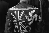 The back of a leather clad Punk Rocker with 'God Save The Queen' a swastika and a Union Jack decorating the jacket